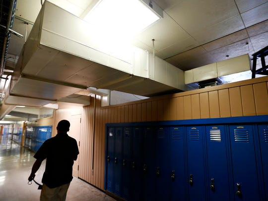 A student walks under an HVAC duct, which is overing