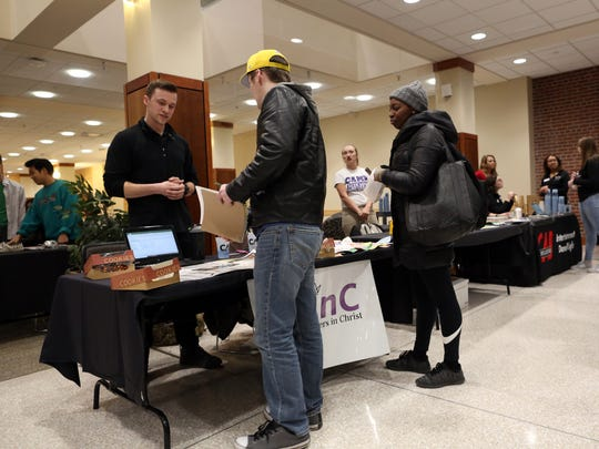 University of Iowa senior Jake Estell, left, chats with students at the Business Leaders in Christ booth during the student organization fair at the Iowa Memorial Union on Wednesday, Jan. 24, 2018.