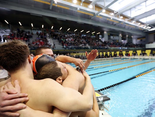 Ames teammates celebrate after clinching the team title