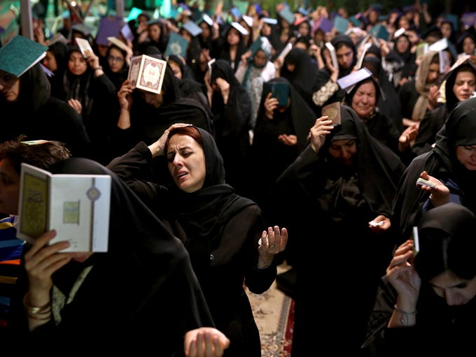 Iranian Shiite Muslims place copies of Quran, Islam's