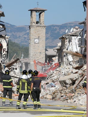 Firefighters stand by rubble in Amatrice, Italy on