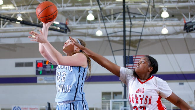 Lansing Catholic's Meghan Gillespie, left, shoots against Sexton's Tori Blackman (33) Monday, Feb. 27, 2017, in Fowlerville, Mich.