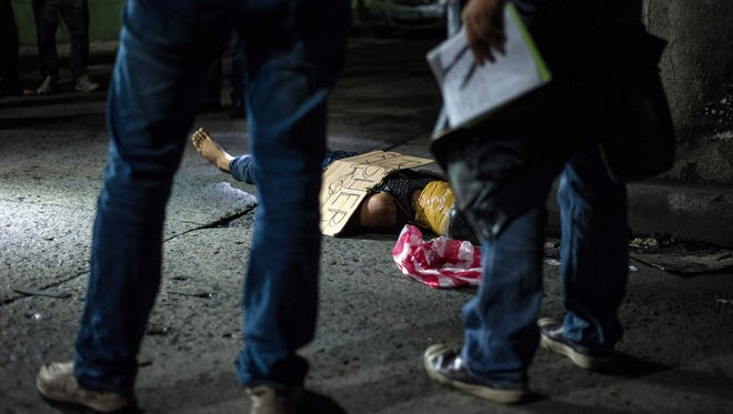 """Philippine police officers investigate the body of an alleged drug dealer, his face covered with packing tape and a placard reading """"I'm a pusher"""", on a street in Manila on July 8, 2016."""