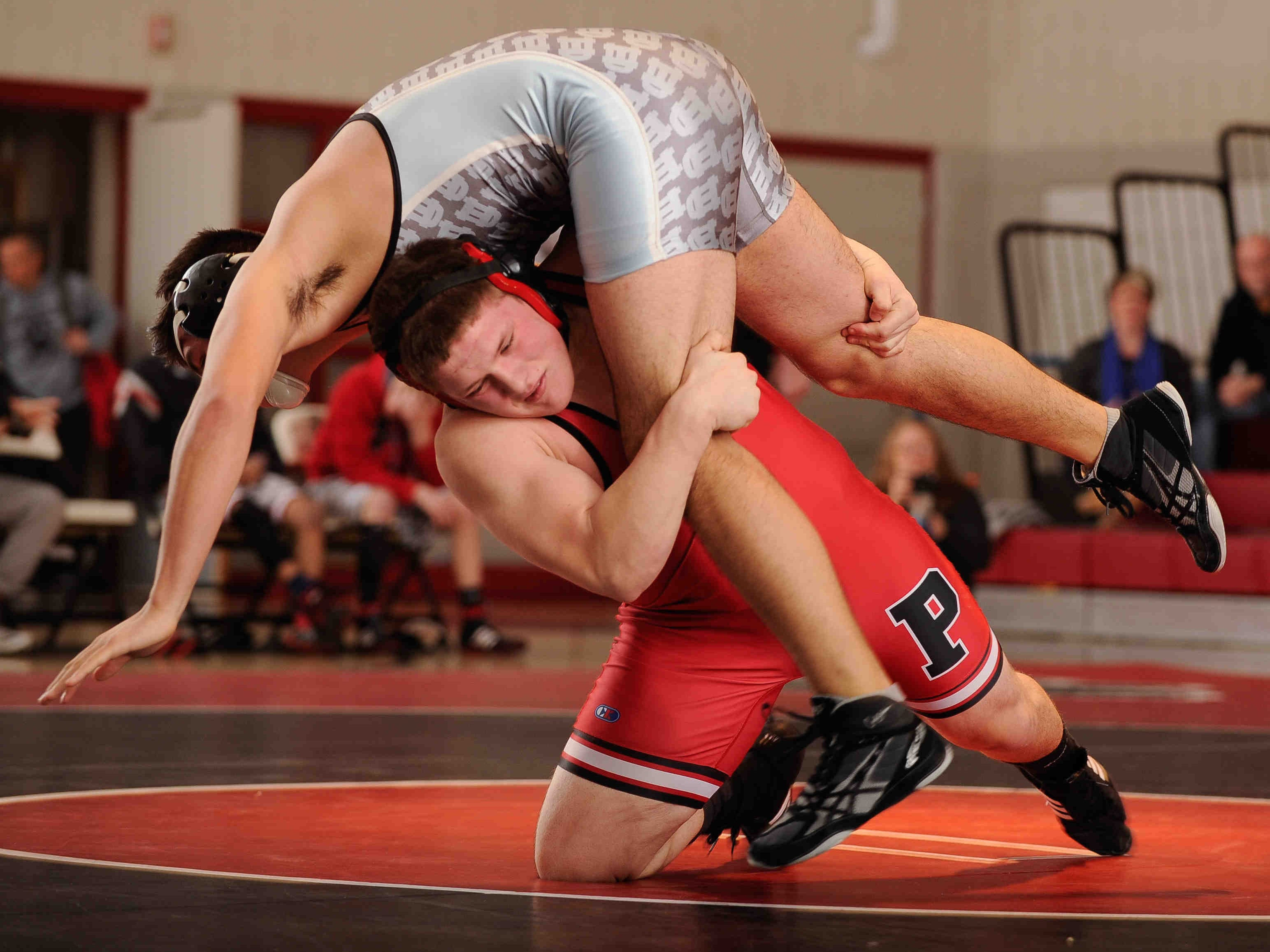 Polytech's Justin Land (bottom) picking up Cape Henlopen's Joel Torres in the 195-pound match.