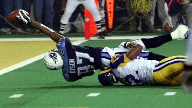 Titans wide receiver Kevin Dyson (87) tries but fails to get the ball into the end zone as he is tackled by the Rams' Mike Jones on the final play of Super Bowl XXXIV.