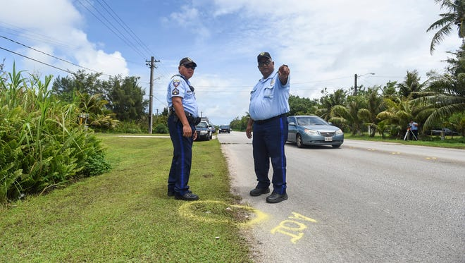 Guam Police Department officers Patrick Sanchez, right, and J.L. Laxamana investigate the scene of an auto-pedestrian crash on Ysengsong Road in Dededo on June 4, 2018.