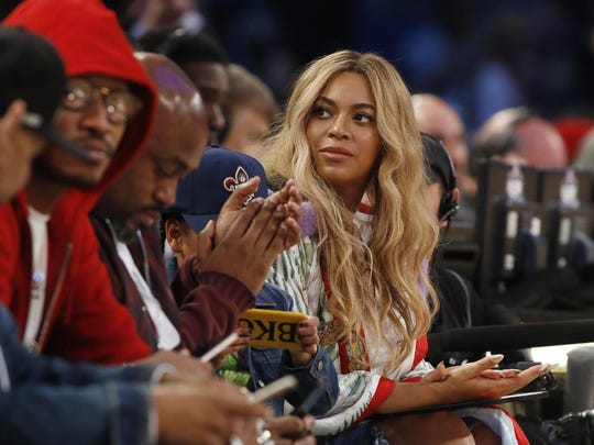"FILE - In this Feb. 19, 2017. file photo, Beyonce sits at court side during the second half of the NBA All-Star basketball game in New Orleans. Netflix on Sunday, April 7, 2019 posted on its social media channels a yellow image with the word ""Homecoming"" across it. The only other information was a date: April 17. That's when Netflix is expected to premiere a Beyonce special that may feature her performances at last year's Coachella Valley Music and Arts Festival. (AP Photo/Max Becherer, File)"