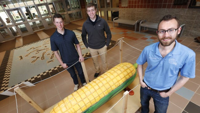 Engineers Without Borders-ISU will auction the folk art coffin by Eric Adjetey Anang to help fund an earthen dam in Ghana. From left, engineering students Kevin Strohm, Jason Schmitt and Joe Gettemy.