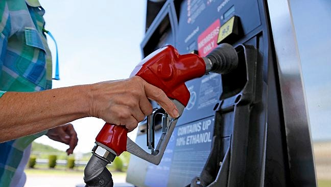 A woman holds a nozzle as she refuels her car on July 16, 2015, at a Costco gas station in Robinson Township, Pa. Prices for coal, natural gas, oil and the fuels made from crude such as gasoline and diesel are all far less expensive than they have been in recent years, delivering big breaks for consumers and decimating energy company profits and leading to huge layoffs.