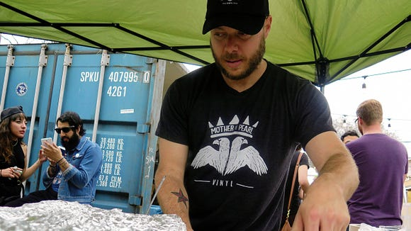 Austin Allen, co-owner of Mother of Pearl Vinyl, serves up orders of free Chico's Tacos at the Mother of Pearl 2015 Unofficial SXSW Showcase in Austin. The record store will return to the state capital for the third year on Thursday to showcase El Paso music, food and culture.