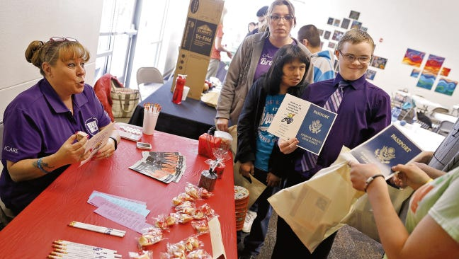 Dina Tingley, an employee of disability services at San Juan College, talks with students on April 24, 2015, during the Youth Transition Fair at the San Juan Center for Independence in Farmington.
