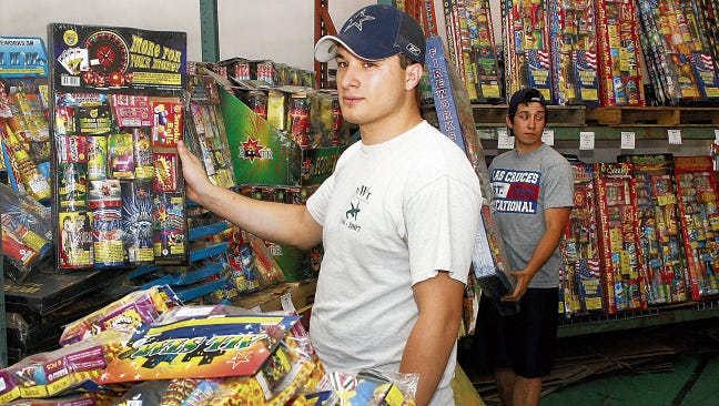 Customers browse fireworks from a vendor in 2014, the last year the city imposed place-of-use restrictions. Monday, the council voted to restrict fireworks use to paved or barren surfaces or places near water. Fireworks sales begin June 20.