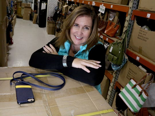 Kelly Carroll Burgin is photographed with an iPhone case that was featured in O Magazine favorite things for Christmas 2016. She is inside the warehouse of her business called K. Carroll Accessories in Auburn Hills on Friday, December 2, 2016.