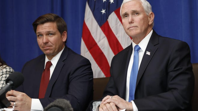 Vice President Mike Pence, right, and Florida Gov. Ron DeSantis take questions during a Florida coronavirus response meeting at the West Palm Beach International Airport, Feb. 28.
