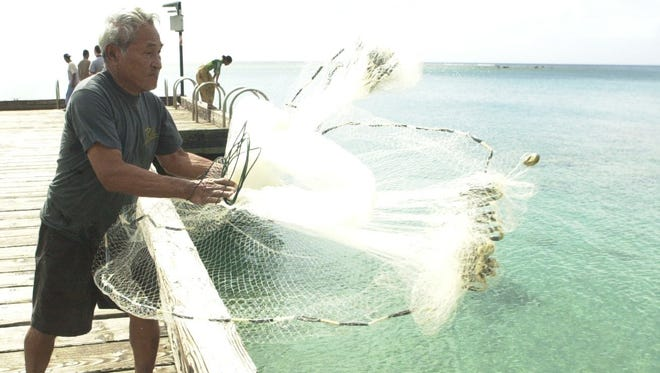 Bernabe Barcinas, of Merizo, throws his net out onto Cocos lagoon, Tuesday in an attempt to catch fish in this 2003 file photo.