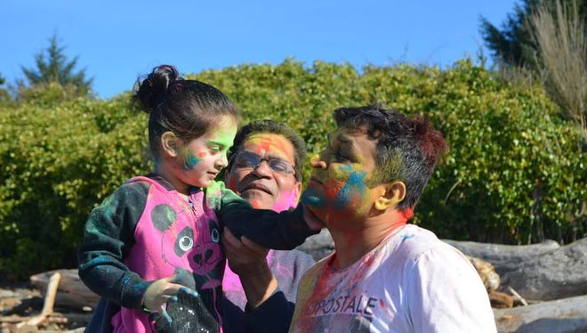 Jiya Patel, left, her father Kamlesh Patel and cousin Dikshant Patel smear colors on one another during a celebration of Holi last year. The Indian festival of colors and sharing love includes song, dance and covering others in color. INDUS will host a Holi celebration March 12 at Columbia Hall at the Oregon State Fairgrounds.