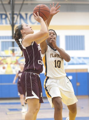 Holy Cross' Molly Britton, left, shoot over Florence's Mattison Worthy during Thursday's game.