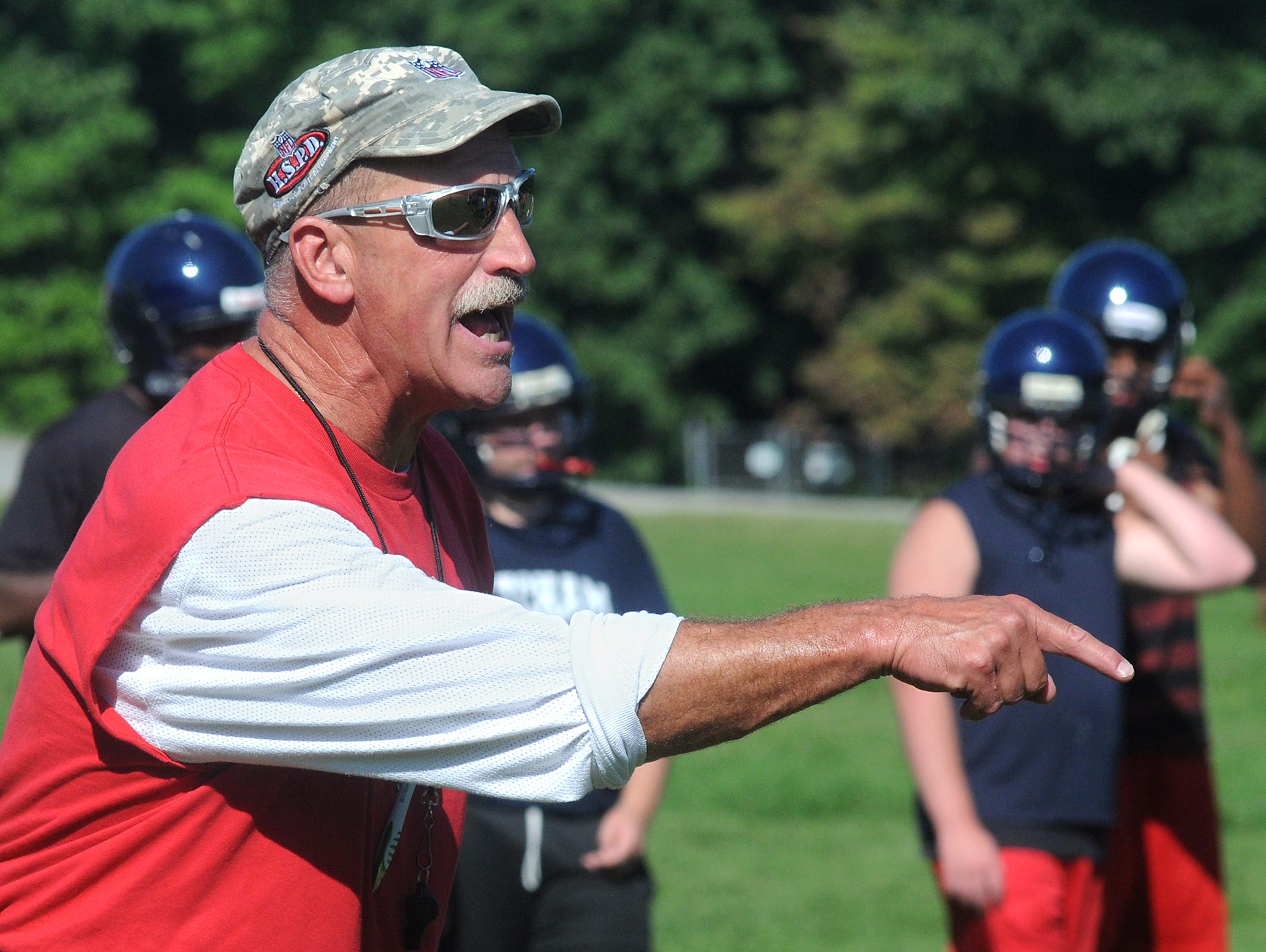 Bill Roos, the new Roy C. Ketcham High School football coach, leads his team through a variety of drills Monday on the first day of practice in Wappingers Falls.