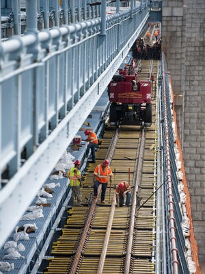 Workers replace the wooden ties and steel rails on the eastbound track of the PATCO Hi-Speedline on the Benjamin Franklin Bridge on Wednesday, July 9, 2014.
