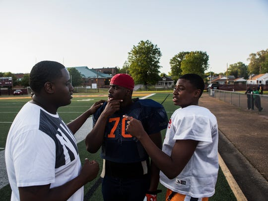 April 27, 2018 - Coach Abraham Austin, left, with Freedom Prep Academy, and Chris Morris, a left tackle for Freedom Prep Academy, listen to Tevin Carter, 15, as he speaks from the sideline during a scrimmage against Melrose High School at Melrose Stadium on Friday. Carter, a rising freshman quarterback with Pure Youth, an organization that focuses on football, education, and character, is fielding offers from three major colleges.