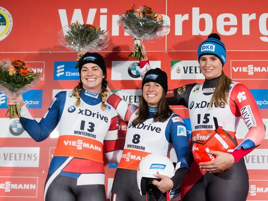 United States second place winner Summer Britcher, United States' winner Emily Sweeney and Germany's third placed Natalie Geisenberger, from left, celebrate on the podium  after the women's singles race event at the Luge World Cup in Winterberg, Germany, Sunday, Nov. 26, 2017.