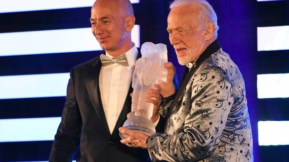 Jeff Bezos of Blue Origin receives the Buzz Aldrin Space Innovation Award from its namesake during Saturday's Apollo 11 Anniversary Gala at the Apollo/Saturn V Center.
