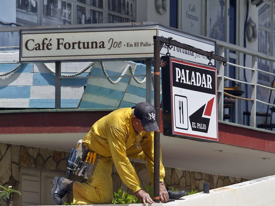 A man performs maintenance work outside a private restaurant