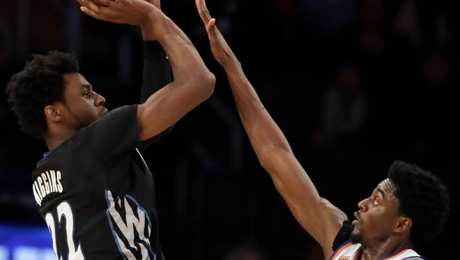 Minnesota Timberwolves forward Andrew Wiggins (22) shoots against New York Knicks guard Justin Holiday (8) during the second half of an NBA basketball game at Madison Square Garden in New York, Friday, Dec. 2, 2016.