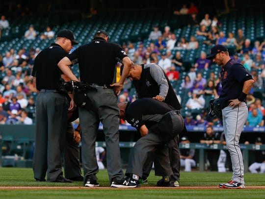 Home plate umpire Mike Everitt stands bent over while