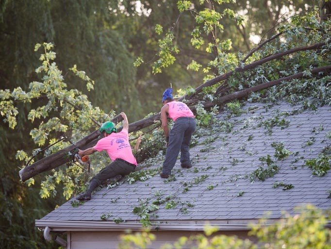 A crew cleans up tornado damage from an EF-1 event that damaged several homes in western Plainfield and eastern Indianapolis, a day earlier, Wednesday, June 25, 2014.