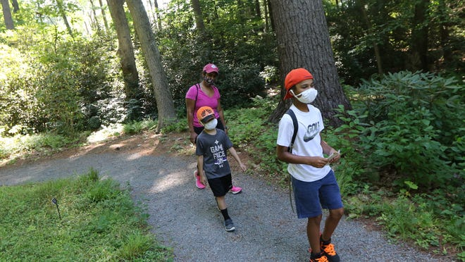 The Moulton family, of Natick, Jai, 11, Devan, 6 and mom, Usha, walk the paths of the Garden in the Woods, in Framingham Wednesday morning, July 29, 2020.