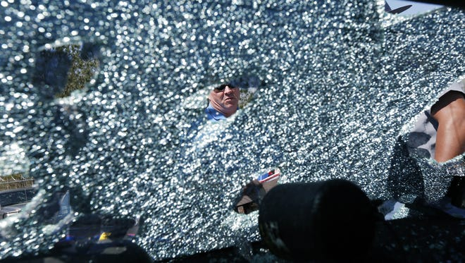 Mississippi Highway Patrol Lt. Col. Mike Holmes peers into the shattered back window of a cruiser in Pearl in this March 19, 2013, photo. Some 65 Highway Patrol fleet backup vehicles were severely damaged by the hail storm, as were a number of other service vehicles in central Mississippi.