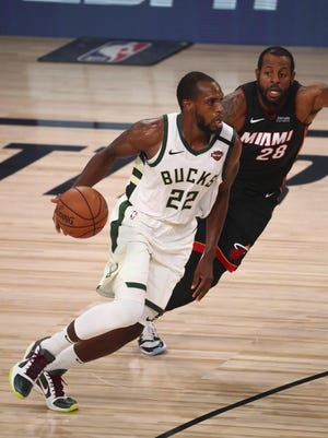 August 6, 2020; Lake Buena Vista, Florida, USA; Milwaukee Bucks forward Khris Middleton (22) moves the ball against Miami Heat guard Andre Iguodala (28) during the second half of an NBA basketball game Thursday, in Lake Buena Vista, Fla.
