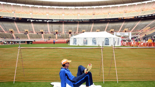 A runner stretches near the finish line in Neyland Stadium of the Covenant Health Knoxville Marathon on Sunday, March 25, 2018.