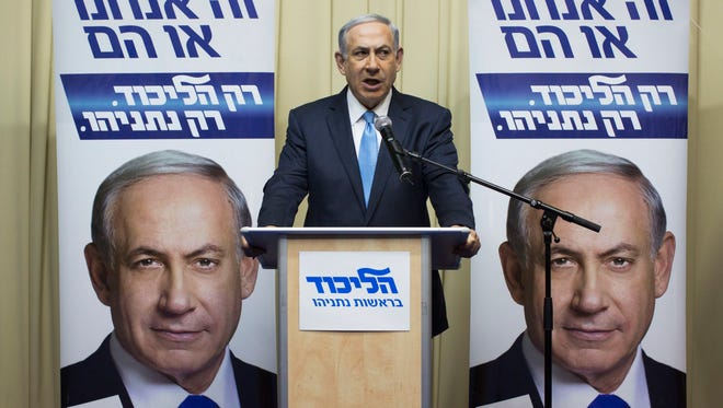 Israeli Prime Minister Benjamin Netanyahu, leader of the Likud Party, speaking from his Jerusalem residence before a backdrop of his Likud campaign posters as he addresses Israelis on television and asks them to vote on March 17, 2015.