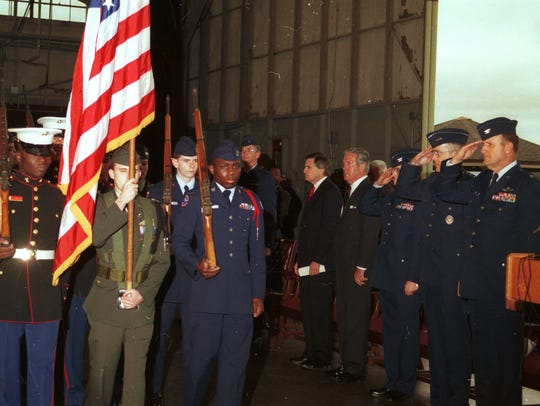 A color guard carries the American flag past a group