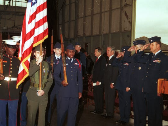 A color guard carries the American flag past a group of dignitaries during the ceremonies to close England Air Force Base in 1992.
