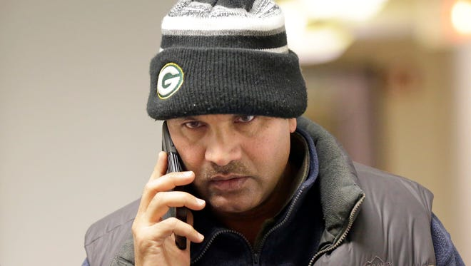 Mohammad Choudry, who owns many properties in Milwaukee's central city, talks on his phone at a sheriff's sale in 2016.