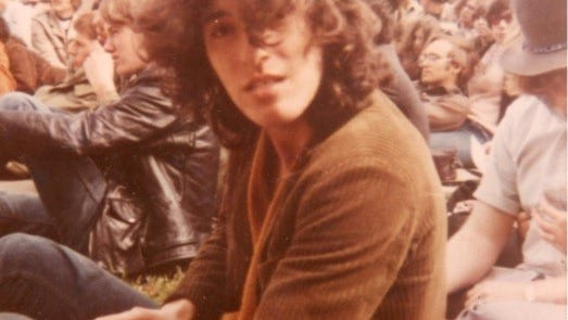 """Bruce Springsteen in the crowd at Monmouth College, watching another band perform before his band, """"Child,"""" takes the stage, 1969."""