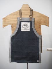 A child's work apron from The Factory Workers line of clothing and accessories is displayed at The Factory in Collingswood.  The Factory owner Tom Marchetty has launched the clothing and accessories line, and worked hard to have the items produced entirely in the USA.