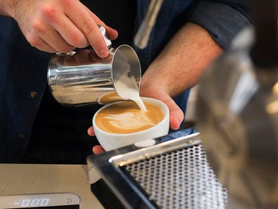 Barista Ryan Riddell pours a latte at Honeybee Coffee