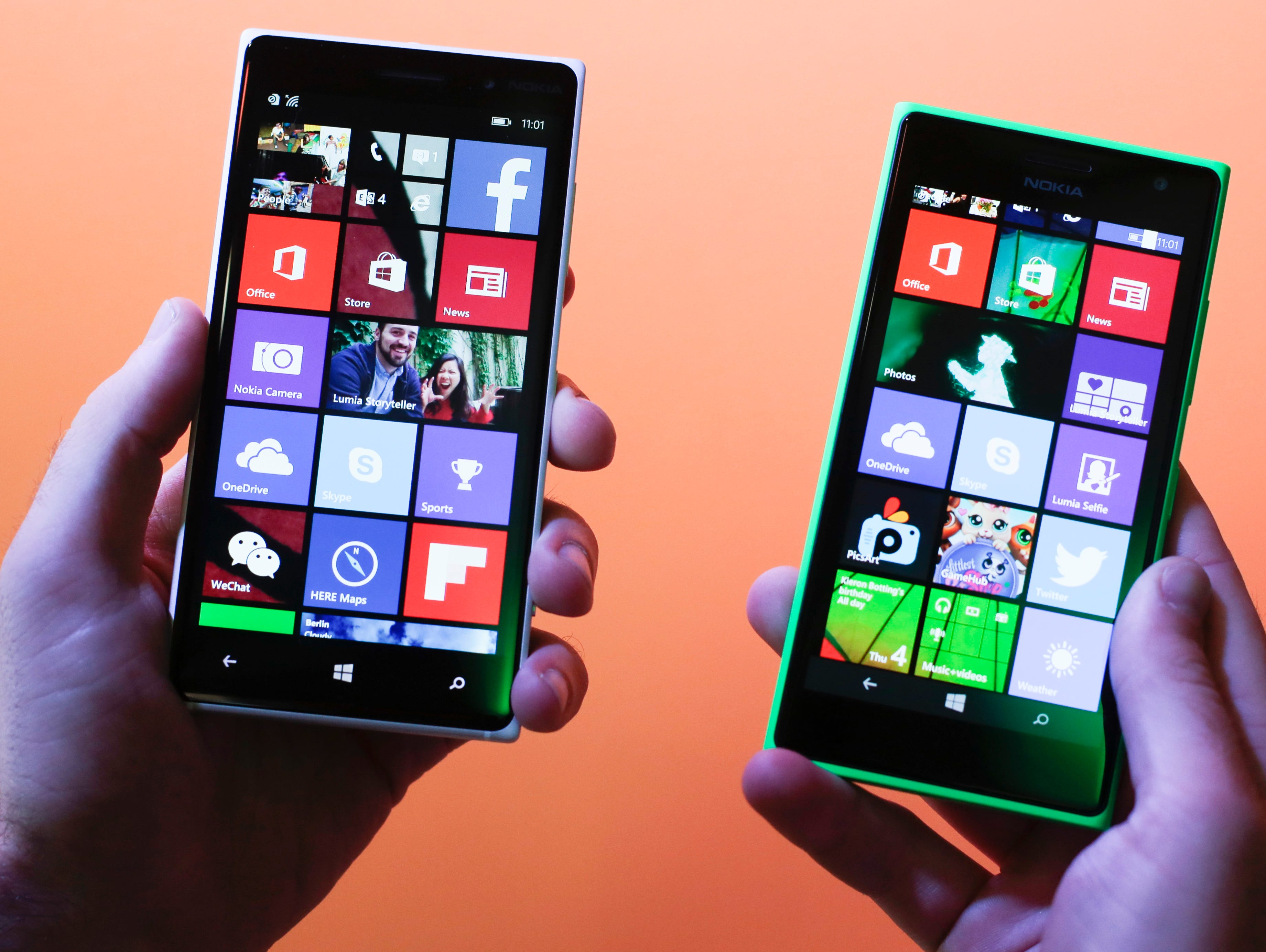 A man shows the Lumia 830, left, and 730, right, smartphones during a Microsoft event at the consumer electronic fair IFA in Berlin.