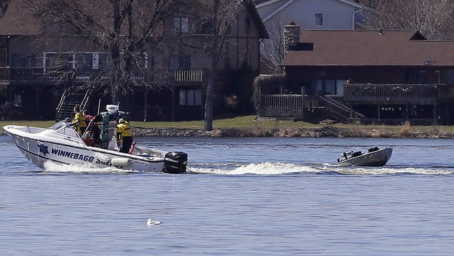 Rescue personnel work near the Ninth Street boat landing on Saturday on Little Lake Butte des Morts in Menasha. Emergency responders arrived on the scene after reports of someone in the water calling for help. An empty boat, still running, was found closer to the west side of the lake.