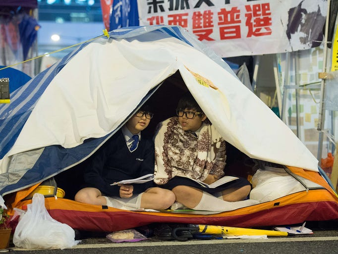 Students read books in their tents at the pro-democracy