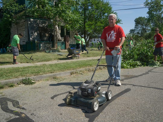 Livonia Mayor Dennis Wright moves a mower to the next