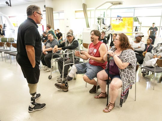 Amputee Walking School co-founder and Paralympic athlete Dennis Oehler, left, takes questions from Daniel and Joni Waters, right, during a session of the class held at the IU Health Neuroscience Center in Indianapolis on Monday, April 17, 2017.