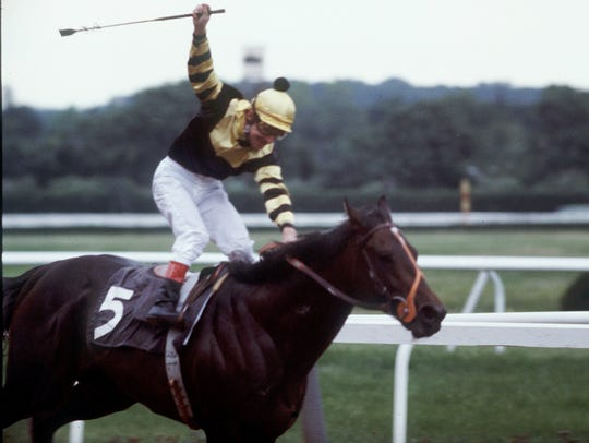 Jockey Jean Cruget stands up in his saddle and celebrates