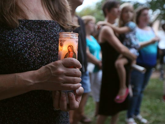 Stacy Palmer holds a candle during a candlelight vigil