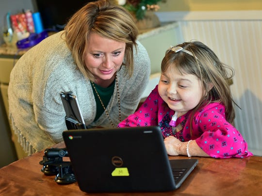 Reese Burdette studies with help from her mom, Claire, at her Mercersburg home. Burdette recently received a new kidney and is back home, getting ready for the holidays.