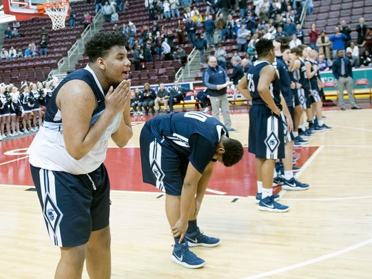 Joel Torres, left, watches as Reading players celebrate. Chambersburg battled Reading for the PIAA D3 6A basketball title on Saturday, March 3, 2018. The Red Knights won 46-43.